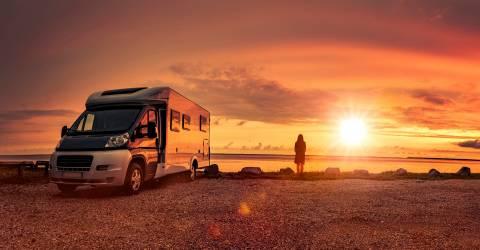 Vrouw bij zonsondergang met stacaravan op het strand