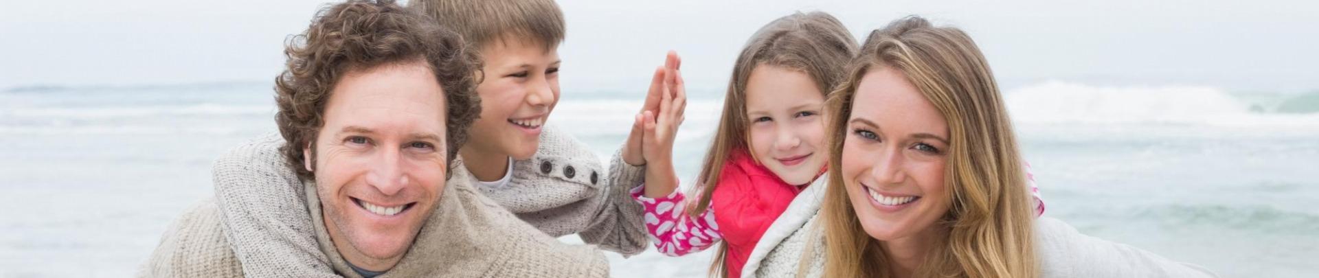 Gezin op het strand ouders met kinderen op hun rug